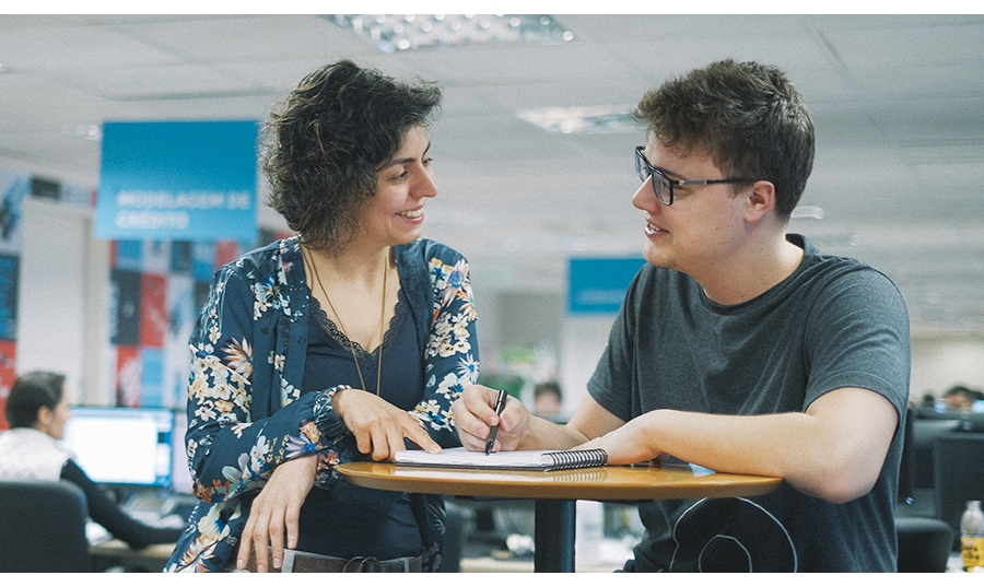 Uma mulher e um menino apoiados numa mesa, conversando.