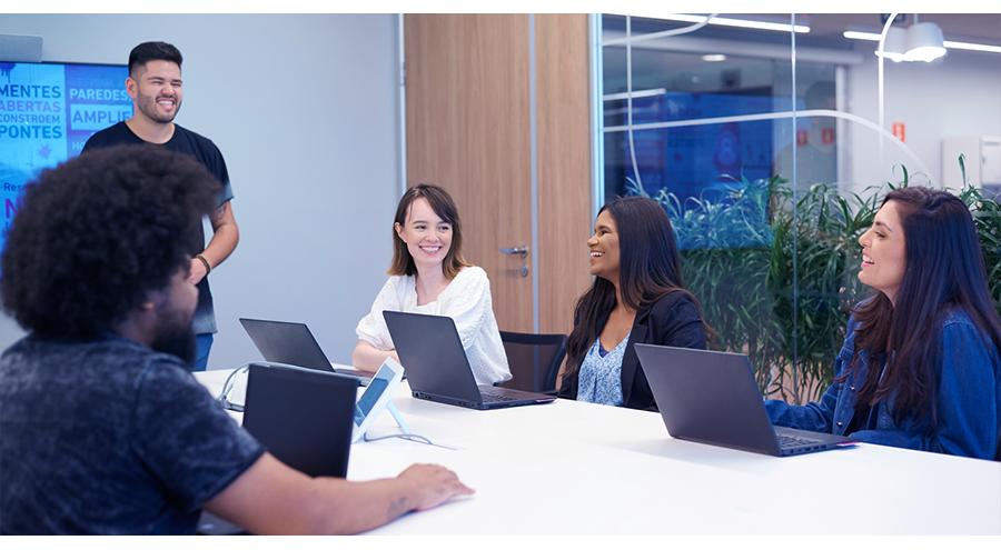 Em uma sala de reuniões com TV, porta de madeira e vidro com visão de plantas atrás, vemos um homem em pé e três mulheres e um homem sentados com notebooks. Todos estão sorrindo.